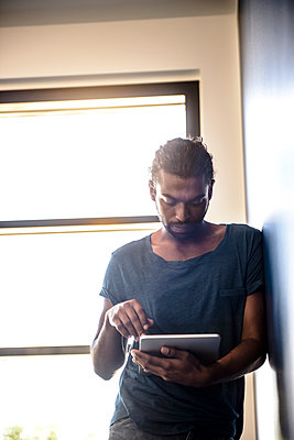 Young man using digital tablet while leaning on wall - p300m2281525 by Buero Monaco