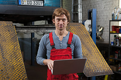 Portrait of mechanic holding laptop at garage - p301m1070020f by Halfdark