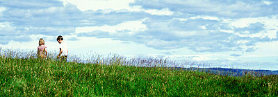 Back view of two children walking in a grassy field - p3483712 by Kristjan Maack