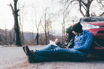 Hiking couple sitting on roadside looking at map, Monte San Primo, Italy - p429m1448313 by Eugenio Marongiu