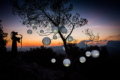 Witch and lampions at sunset - p829m2295591 by Régis Domergue