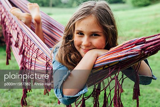 Portrait of smiling girl lying in hammock - p300m1587382 von Annie Hall