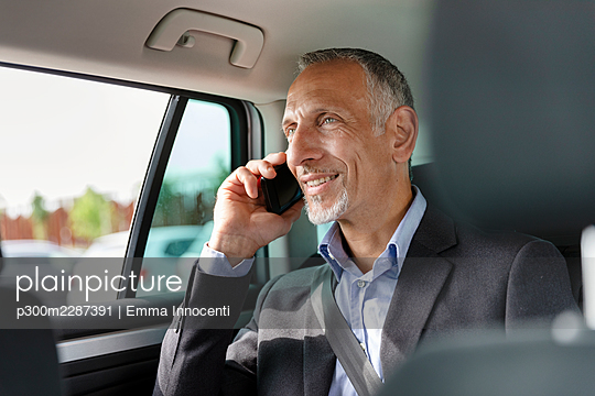 Male professional talking on mobile phone while sitting in car - p300m2287391 by Emma Innocenti