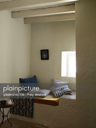 Striped cushions on window seat in Spanish home - p349m2167735 by Polly Wreford