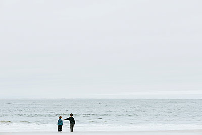 Rear view of brothers standing at beach against sky - p1166m1521011 by Cavan Images