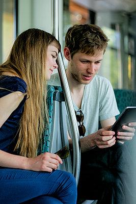Junges Paar in der Bahn schauen auf dem Tablet  - p1212m1138818 von harry + lidy