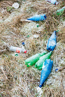 Green, blue, and clear plastic drinks bottles littering an area of snow covered grass - p1302m1591688 by Richard Nixon