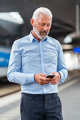 Mature businessman using cell phone at the station platform - p300m2118887 by Daniel Ingold