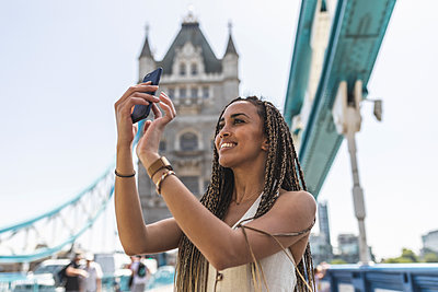 Portrait of happy young woman taking selfie with smartphone on Tower Bridge, London, UK - p300m2132654 by William Perugini