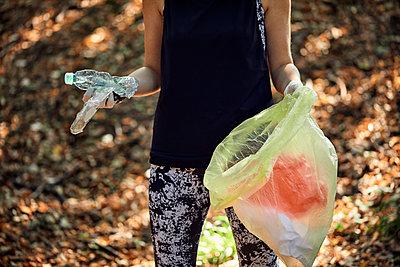 Woman plogging in forest - p300m2140774 von Zeljko Dangubic
