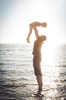 Father lifting up his son on the waterfront - p756m2216298 by Bénédicte Lassalle
