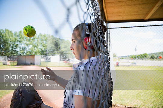 Middle school girl softball player with headphones throwing softball at fence
