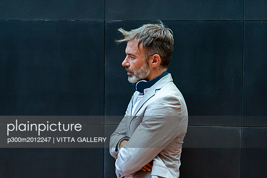 Bearded businessman with headphones in front of black wall - p300m2012247 von VITTA GALLERY