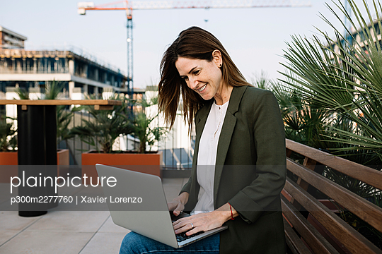 Smiling female entrepreneur using laptop while sitting on bench at building terrace - p300m2277760 by Xavier Lorenzo