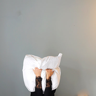 Young woman hiding behind pillow - p1105m2231719 by Virginie Plauchut
