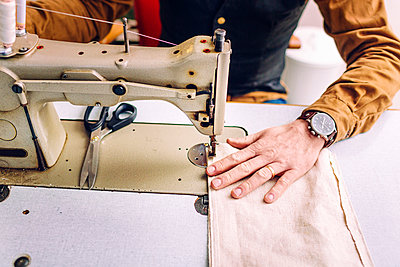Midsection of male worker sewing bag pocket in workshop - p1185m994122f by Astrakan
