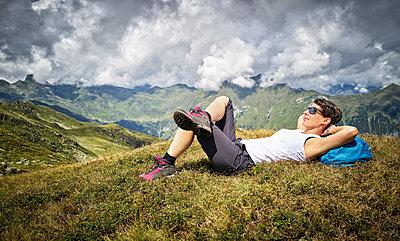 Woman having a break from hiking lying on alpine meadow, Passeier Valley, South Tyrol, Italy - p300m2155620 by Dirk Kittelberger