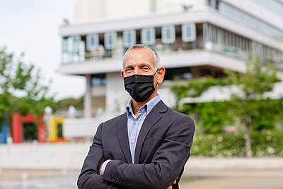Businessman with protective face mask near building in city during COVID-19 - p300m2287334 by Emma Innocenti