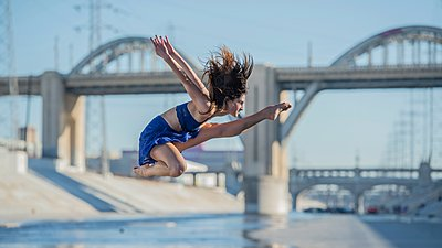 Side view of dancer jumping in mid air in front of bridge, Los Angeles, California, USA - p429m1105721 by Pete Saloutos