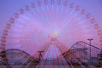 Double exposure of ferris wheel and roller coaster - p555m1231914 by Julien McRoberts