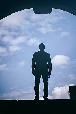 Silhouette of a man standing against a blue sky  - p794m1562165 by Mohamad Itani