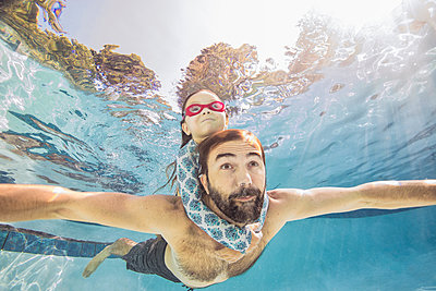 Underwater view of mature man swimming with daughter on piggy back - p924m1493832 by Romona Robbins Photography