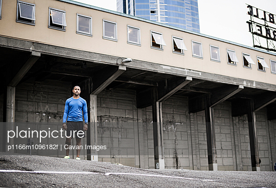 Man wearing sports clothing standing in front of old building