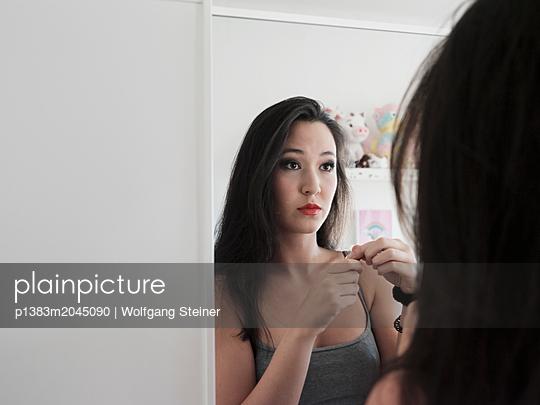 Junge Frau trägt Make-Up auf - p1383m2045090 von Wolfgang Steiner