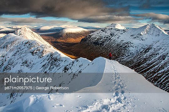 A female walker approaching the summit of Stob Dubh on Buchaille Etive Beag on a crisp winter day, Highlands, Scotland, United Kingdom - p871m2057975 by George Robertson