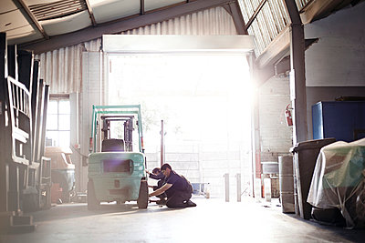 Mechanics repairing forklift in auto repair shop - p1023m1058924f by Trevor Adeline