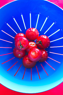Top view of three tomatoes in a blue strainer - p1166m2107814 by Cavan Images