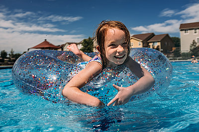 center shot of young girl floating in neighborhood pool - p1166m2182721 by Cavan Images