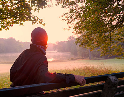 Mature woman looking at sunrise view while sitting in public park - p300m2220984 by Hans Mitterer