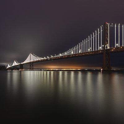 Illuminated Oakland Bay Bridge at night in San Francisco, California, USA - p300m2242201 by Alex Holland