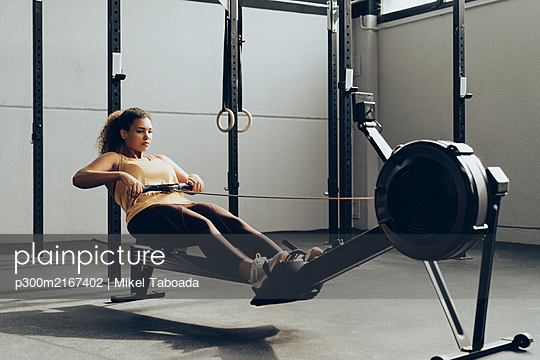 Young woman exercising in gym with rowing machine - p300m2167402 by Mikel Taboada