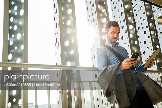 Young businessman holding cell phone and digital tablet - p300m2219565 by Uwe Umstätter
