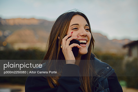 Laughing beautiful woman talking on smart phone with mountains in background - p300m2250083 by Aitor Carrera Porté