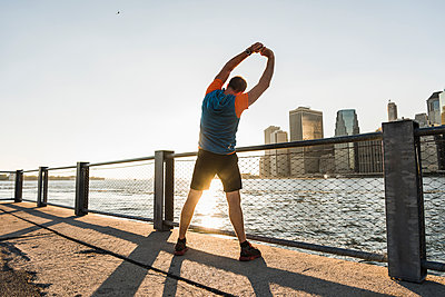 USA, Brooklyn, back view of man doing stretching exercises in the evening - p300m1205934 by Uwe Umstätter