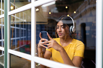 Beautiful young woman listening music while using smart phone at bar seen through window - p300m2221054 by Sus Pons