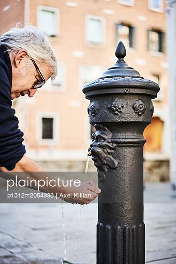 Mann erfrischt sich an einen Brunnen - p1312m2054993 von Axel Killian