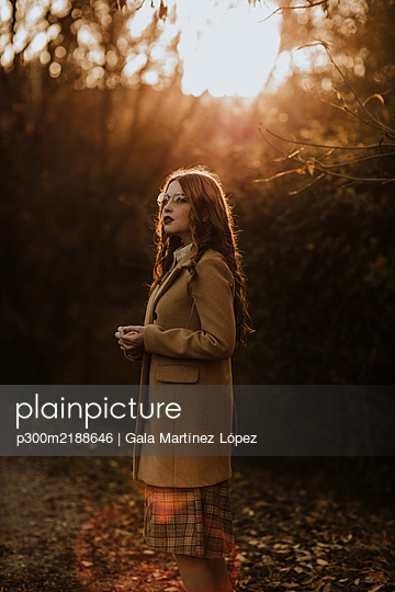 Portrait of fashionable woman in autumn standing at backlight - p300m2188646 by Gala Martínez López