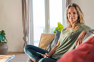 Portrait of smiling woman realxing on couch at home with tablet - p300m2104417 by Steve Brookland