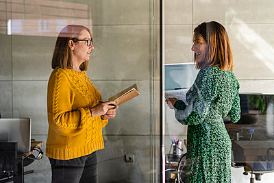 Smiling mature businesswoman with laptop talking to female colleague while standing in cabin - p300m2265404 by Javier De La Torre Sebastian
