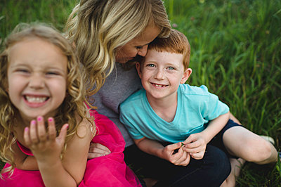 Portrait of girl and brother sitting on mothers lap in grass - p429m1504616 by Erin Lester