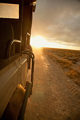 A Land Rover drives through Amboseli National Park at dawn, Kenya - p429m802675 by Cultura