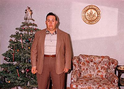 Serious Caucasian man posing near Christmas tree - p555m1444174 by PBNJ Productions