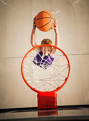 Caucasian boy dunking basketball in hoop - p555m1452629 by Mike Kemp