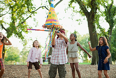 Boy at birthday party hitting pinata - p9245614f by Image Source