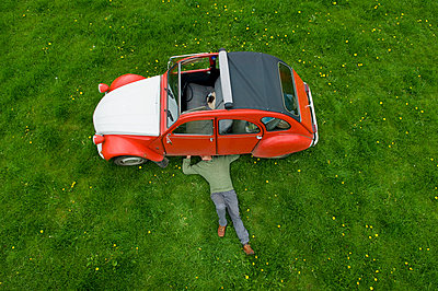 A man lying on his back under a red car, inspecting the underside of the car.  - p1100m923423f by Henry Arden