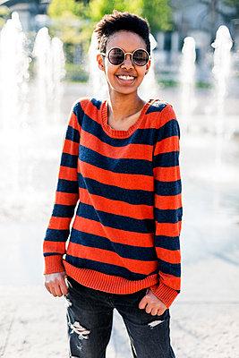 Portrait of smiling young woman wearing  sunglasses and striped pullover - p300m2029231 von Giorgio Fochesato
